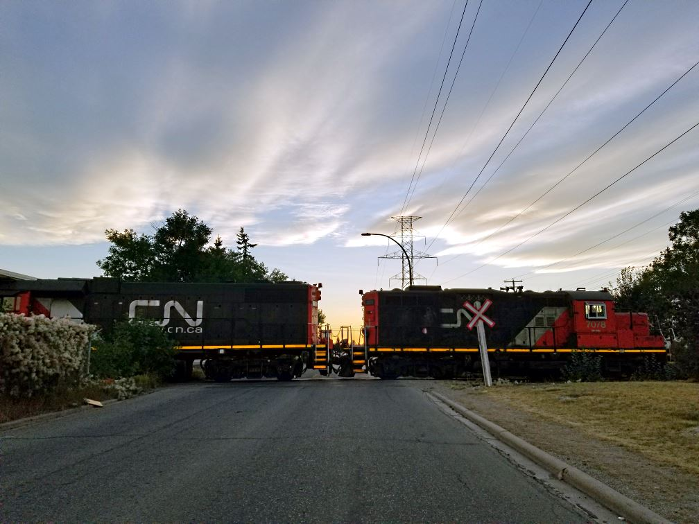 A CN Rail train crossing 34 Ave SE in Calgary. Although there's a level crossing there and a siding, it's not often that you see the train crossing the road. It's still best to assume it might be there though.